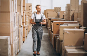 young-man-working-warehouse-with-boxes_1303-16597